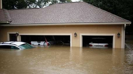 A house and vehicles stand in Harvey's floodwaters