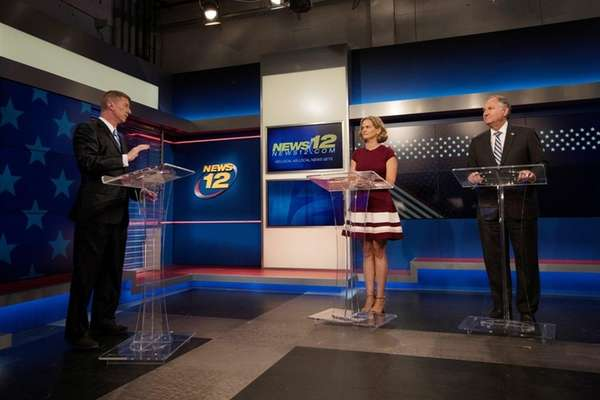 News 12's Stone Grissom, left, prepares to moderate