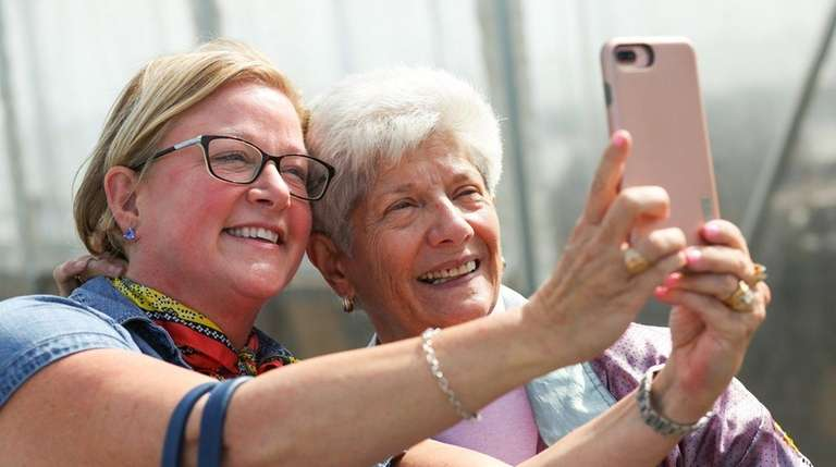 Kitty Liell of Bloomington, IN, left, snaps a