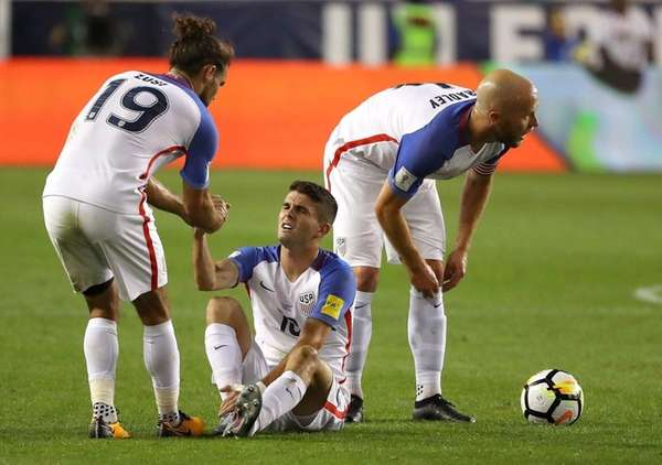 Christian Pulisic of the United States is helped