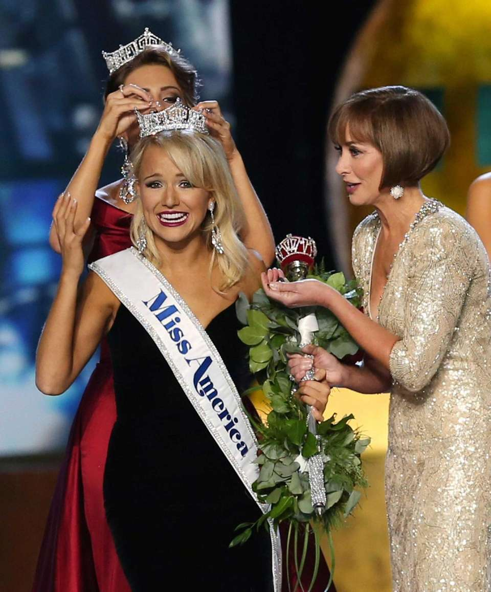 The outgoing Miss America, Betty Cantrell, back, crowns