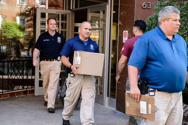 Members of the NYPD Crime Scene Unit carry evidence