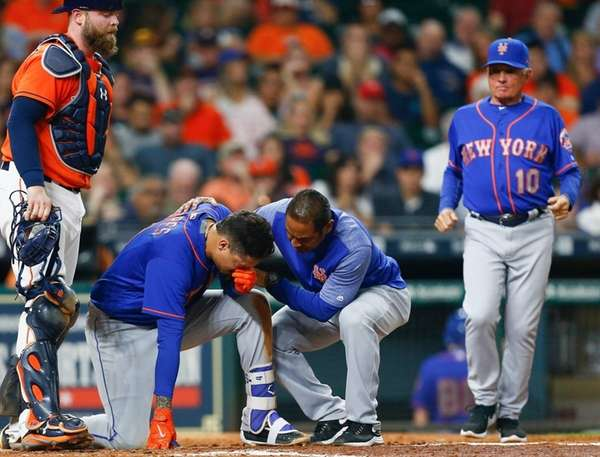 Wilmer Flores is tended to by the Mets