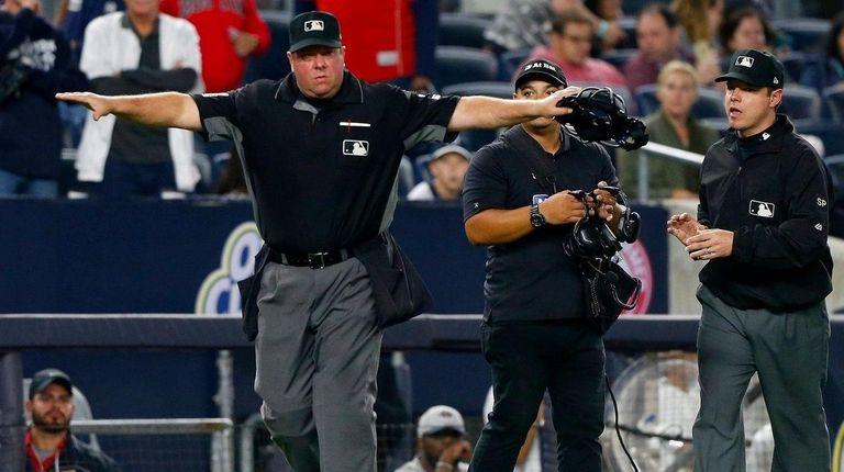 Home plate umpire Sam Holbrook signals safe after