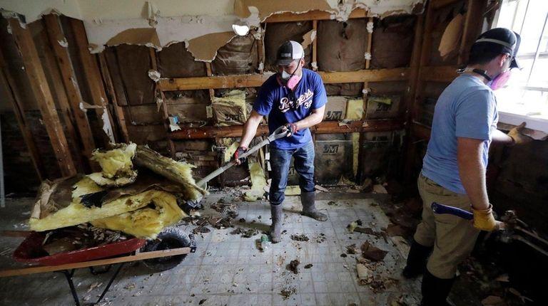 Volunteers Brock Warnick, right, and Colten Roberts remove