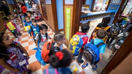 Young students enter their classrooms on the first