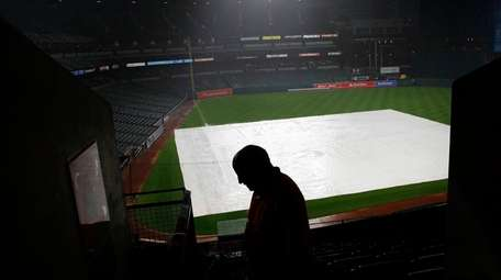 A tarp covering the infield is seen past