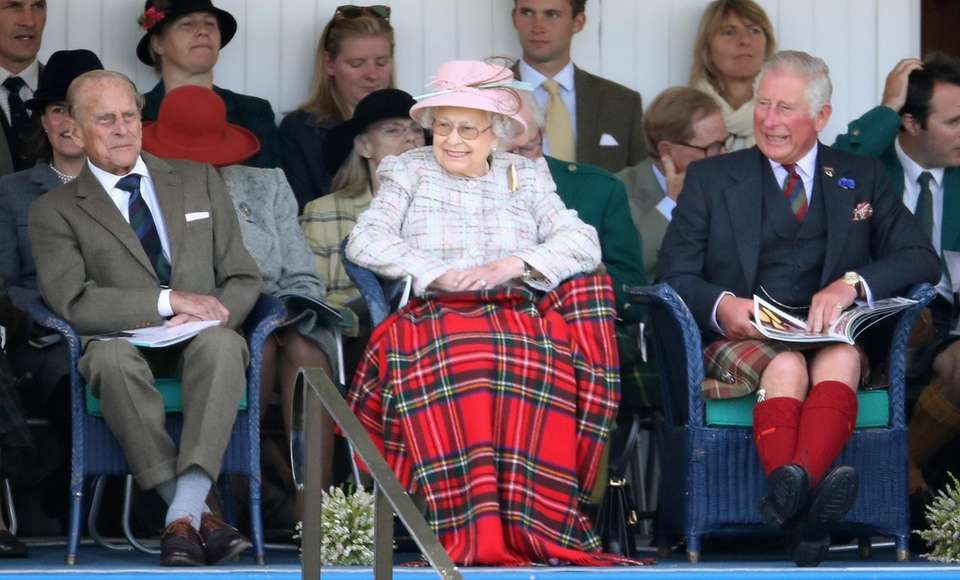 Queen Elizabeth II is flanked by Prince Philip,