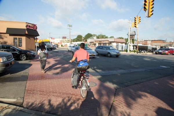 Cars, pedestrians, and cyclists navigate the intersection of