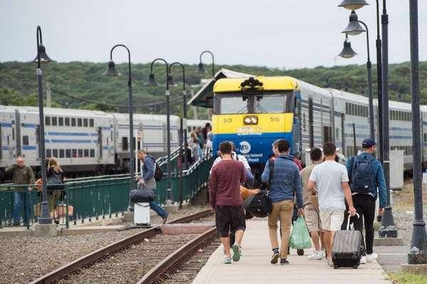 People walk towards an LIRR train as they