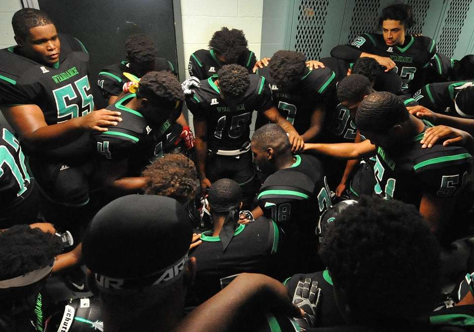 The Wyandanch varsity football team gathers in the