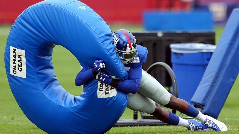Giants defensive end Jason Pierre-Paulhits a tackling donut