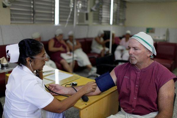 A nurse checks a patient's blood pressure at