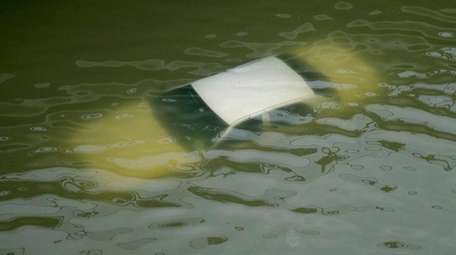 A car is submerged on a freeway flooded