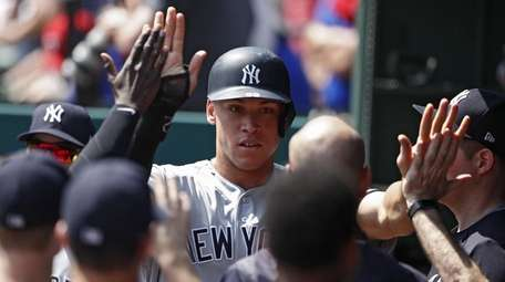 Aaron Judge celebrates with teammates after scoring the