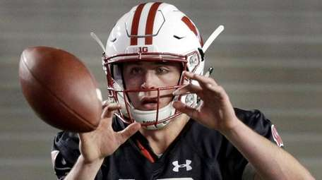 Wisconsin quarterback Jack Coan takes a snap during