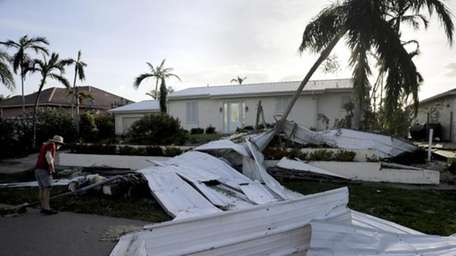 A roof is strewn across a home's lawn