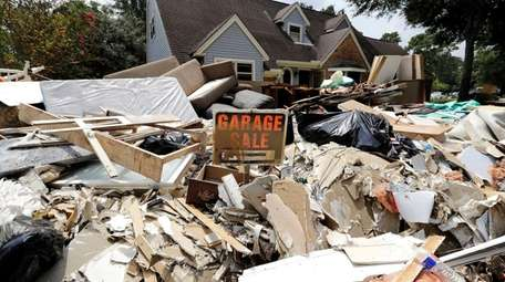 A garage sale sign stands in a pile