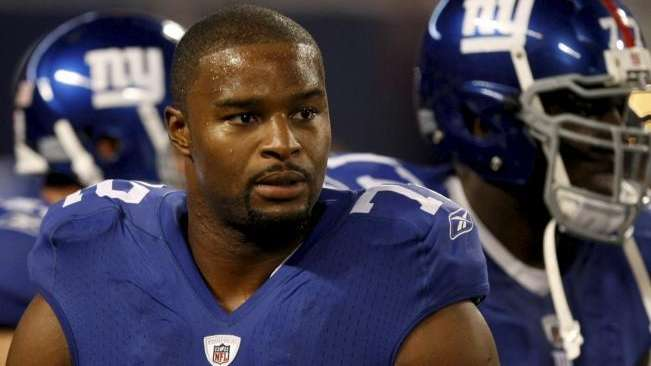 Giants defensive end Osi Umenyiora looks on during
