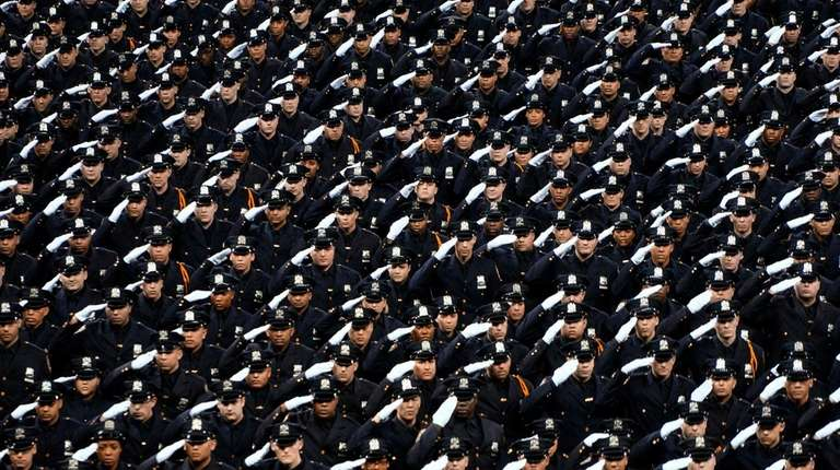 Cadets salute during the NYPD Police Academy graduation