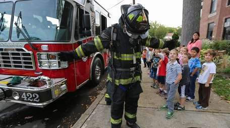A Lynbrook firefighter displays protective gear to students