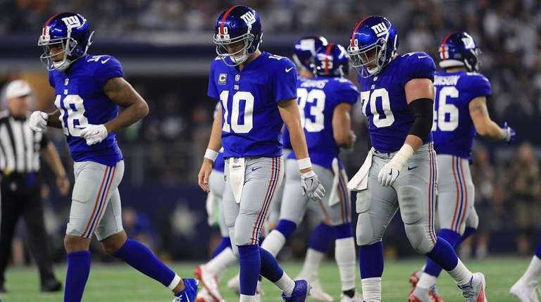 The Giants offense walks off the field during