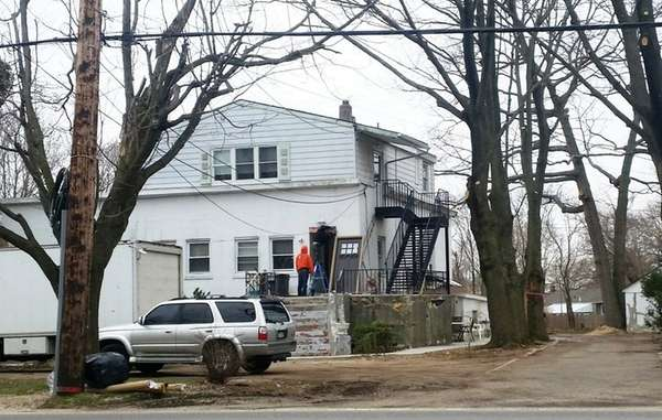 Men perform work on a house on Larkfield
