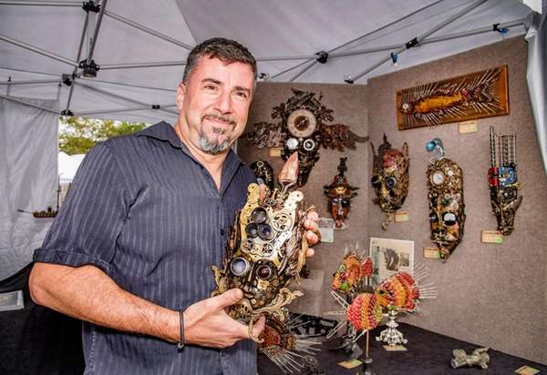 Artist Larry Agnello, holds up one of the