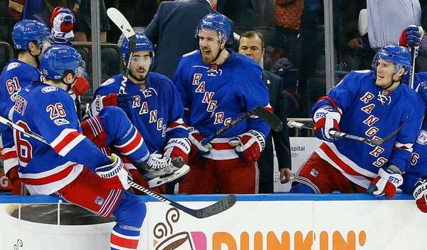 The Rangers celebrate on the bench after defeating