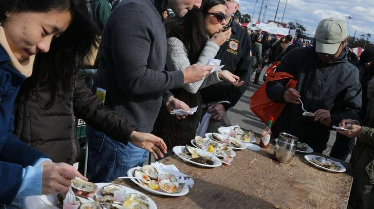 Visitors chow down on plates of oysters at