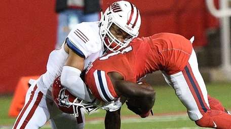 Sacred Heart cornerback Tim Johnson tackles Stony Brook