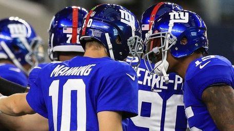 Eli Manning talks with Brandon Marshall, far right,