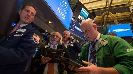 Traders work on the floor at the closing