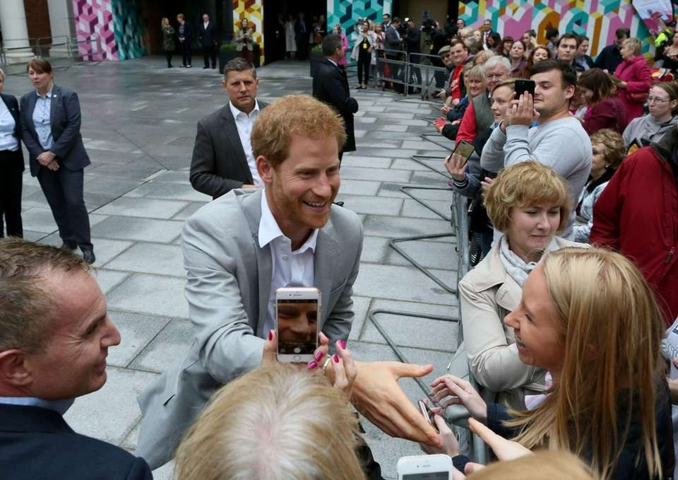 Prince Harry greets people during a walkabout at
