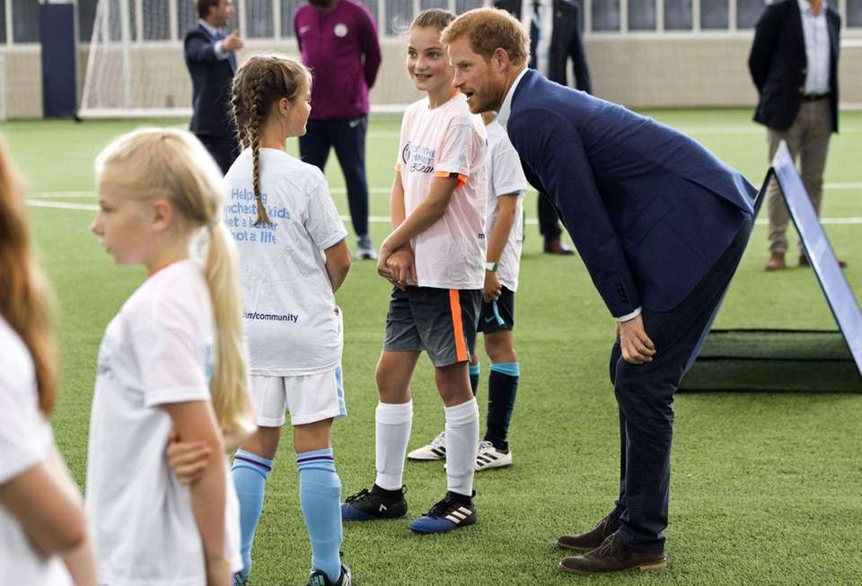 Prince Harry speaks to apprentices as he attends