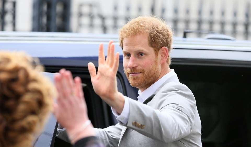 Prince Harry waves as he leaves The MAC