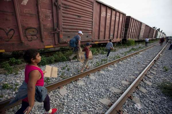 Migrants walk along railroad tracks after getting off