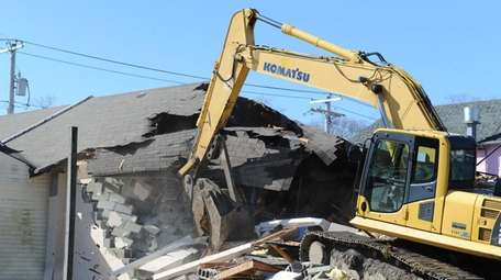 Mastic Beach paramedics look on as the demolition