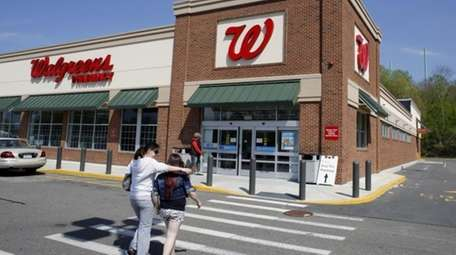 Customers walk toward an entrance to a Walgreens