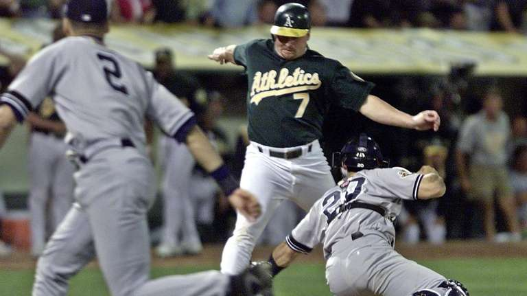 Oakland's Jeremy Giambi, center, is tagged out at