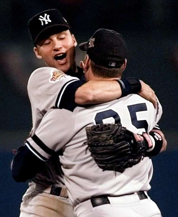 Derek Jeter and pitcher John Wetteland, right, celebrate