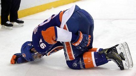 Islanders center John Tavares holdshis left hamstring after