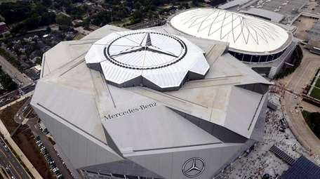 The new Mercedes-Benz Stadium, foreground, stands next to