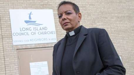 The Rev. Dyanne Pina stands in front of