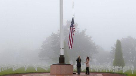 U.S. staff members raise the U.S. flag at