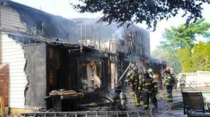 Volunteer firefighters from several communities battle a house