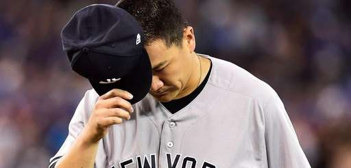 Yankees pitcher Masahiro Tanaka reacts as he is pulled