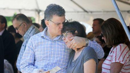 Elliot Katz of Great Neck hugs his wife,