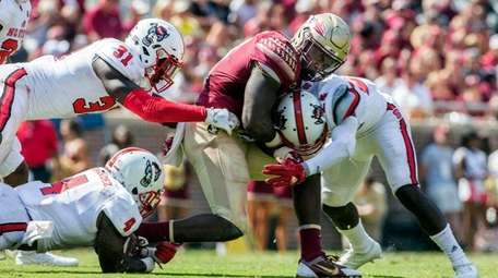 Florida State's Jacquez Patrick grimaces as he's hit