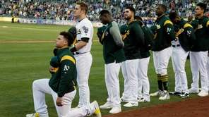 Athletics catcher Bruce Maxwell kneels during the national